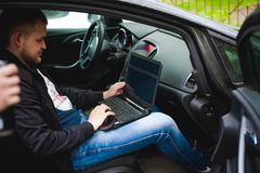 Professional man with a laptop in car tunes tuning control system, updating software, gaining access through to computer Stock Photos