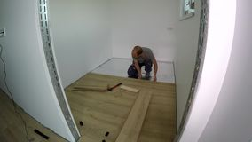 Professional man laying laminate board floor in new apartment room. Timelapse. Shot stock video