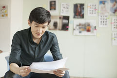 Professional Man Looking at Papers in Office Stock Photo