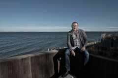 Professional man sat by the sea Royalty Free Stock Photo
