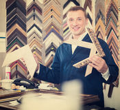 Professional man seller in picture framing studio with wooden de. Professional man seller standing in picture framing studio with wooden details Stock Image