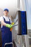 Professional man washes window Royalty Free Stock Photo