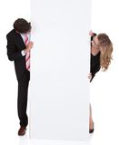Professional man and woman with a blank sign Royalty Free Stock Photo