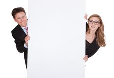 Professional man and woman with a blank sign Royalty Free Stock Image