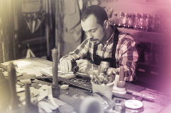 Professional man worker working in leather workshop Stock Image