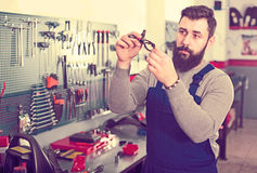 Professional man worker working at restoring motorbike in worksh. Professional man worker working at restoring motorbike in motorcycle workshop Royalty Free Stock Photo