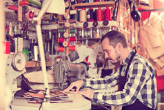 Professional man worker working on stitches for belt. In leather workshop Stock Photos