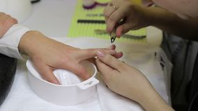 Manucirist cutting cuticle using cuticle scissors stock footage