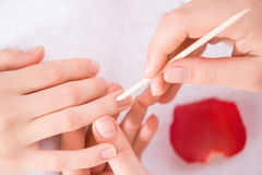 Professional manicurist  making manicure. Best service. Close up of cuticle pusher in hands of professional manicurist holding it while making manicure Royalty Free Stock Photography