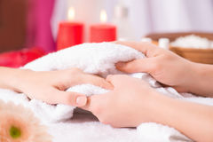 Professional manicurist making manicure. Do it with love. Close of hands of professional manicurist holding hand of the client and holding it on the towel while Stock Photo
