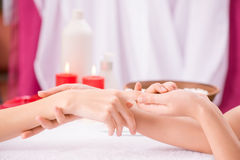 Professional manicurist making manicure. Just relax. Close of hands of professional manicurist holding hand of the client and making massage while going to make Stock Photo