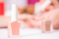 Professional manicurist making manicure. Pleasant color. Selective focus of bottle with nail polish standing on the table with professional manicurist making Royalty Free Stock Photography