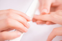 Professional manicurist  making manicure. Working for your pleasure. Selective focus of nail fail  in hands of professional manicurist holding it and making Royalty Free Stock Photo