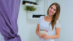 Professional manicurist with nail color palette in nail salon. Multicolored nail polishes in background stock photo