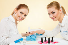 Professional manicurist painting woman nails. Royalty Free Stock Image