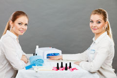 Professional manicurist painting woman nails. Stock Image