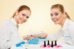 Professional manicurist painting woman nails. Stock Photos