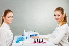 Professional manicurist painting woman nails. Stock Photography