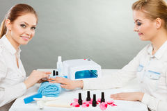 Professional manicurist painting woman nails. Royalty Free Stock Photo