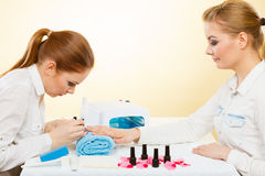 Professional manicurist painting woman nails. Royalty Free Stock Images