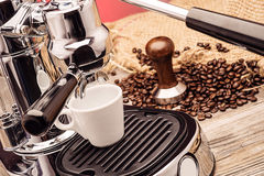 Professional manual silver coffee machine with cup of coffee, stamper and sack coffee beans on red background, product protography Stock Photography