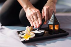 Massage clay cream for body spa. Professional massage female hands holding wooden spa dipper to get clay cream near candle and white Plumeria on the tray Stock Images