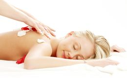 Professional massage with flower petals Royalty Free Stock Image