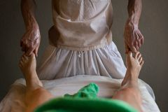 Professional Masseur Doing Deep Tissue Oiled Massage to a Girl at Ayurveda Massage Session. Professional Masseur Doing Deep Tissue Oiled foot Massage to a Girl Royalty Free Stock Image
