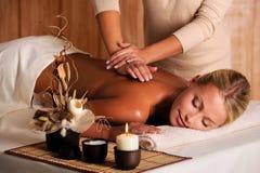 Professional masseur doing massage of female back Stock Photography