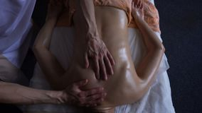 Professional masseur kneads the shoulders of young woman with warm oil on at massage session. top view in ayurvedic