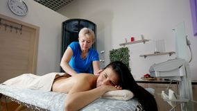 A professional masseur massaging beautful client s back and shoulders with care in a light. Relaxing massage stock footage