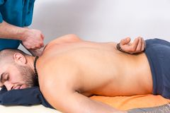 Professional masseur pummelling the back muscles. Of a male client in a clinic using his fist to relax the muscle and any associated knots royalty free stock photo