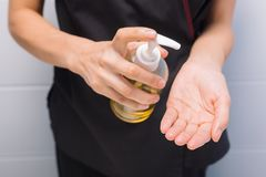 A professional masseur puts oil on his hands before the procedure stock photography