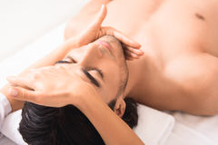 Professional masseuse doing facial massage Stock Image