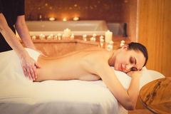 Professional masseuse pampering female body. Relaxed young girl is enjoying back massage at beauty salon. Her eyes are closed with pleasure Stock Photo