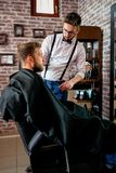 Professional master hairdresser cuts client beard Stock Photos