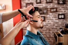 Professional master hairdresser shaves client beard Royalty Free Stock Photos