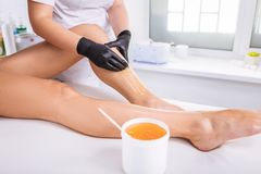 Professional master of wax depilation providing service for client. Master of waxing. Professional skillful master of wax depilation providing service for client royalty free stock images