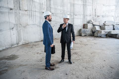 Professional mature architects with blueprint working at construction site Stock Photos