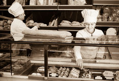 Professional mature bakers with fresh bread in bakery Royalty Free Stock Images