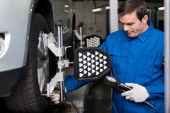 Professional mechanic chacking cars wheel system. Involved in working day. Pleasant professional mechanic standing near car and checking automobile wheel stock photo
