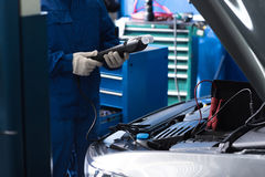 Professional mechanic checking car engine Royalty Free Stock Image