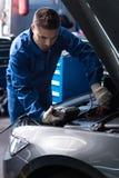 Professional mechanic examining engine Royalty Free Stock Photos