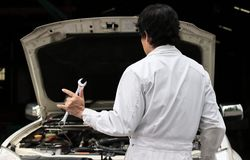 Professional mechanic man holding wrench and his hand with i love you sign with car in open hood at the repair garage. royalty free stock images