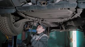 Guy works in car maintanence centre. Professional mechanic is repairing an auto in his own workshop. He is using special tools standing under a vehicle in stock video