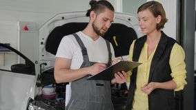 Professional mechanic stands next to open hood car and explains to female customer, problem with engine under hood,. Holding flatbed in order to explain details stock footage