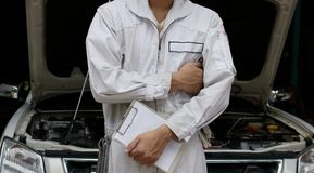 Professional mechanic in white uniform holding clipboard against car in open hood at the repair garage. Maintenance service concep. T Stock Images