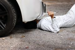Professional mechanic in white uniform lying down and fixing under car. Auto repair service. Professional mechanic in white uniform lying down and fixing under Royalty Free Stock Image