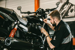 Professional mechanic working screwdriver and motorcycle repairs. Handsome young man repairing motorcycle in repair shop Royalty Free Stock Images