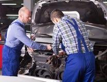 Professional mechanics repairing car Royalty Free Stock Image